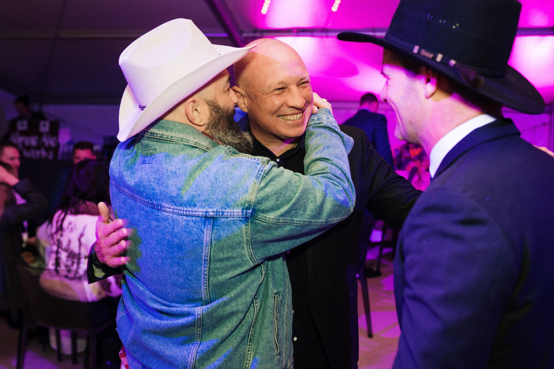 Men in cowboy hats smiling and hugging at event in queenstown.