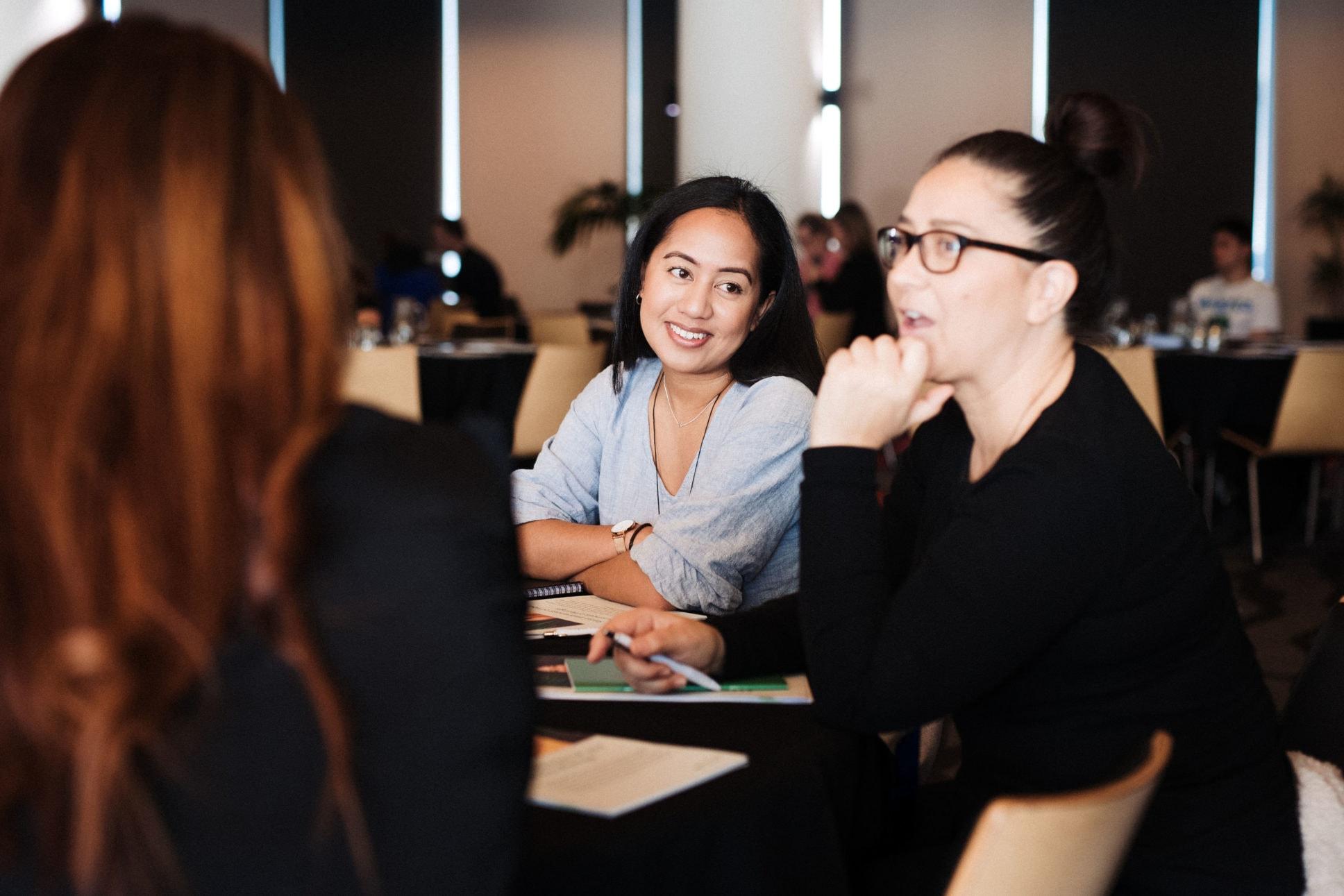 Women laughing at facebook workshop.